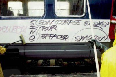 Photo de Matt Jacob – le personnel de la RATP nettoie un tag : « BON COURAGE POUR EFFACER »